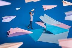 Creatief surrealismeontwerp met origamidocument vliegtuigen Het jonge meisje liet document vliegtuigen Stock Afbeelding