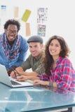 Creatief team die aan laptop samenwerken en bij camera glimlachen Stock Foto