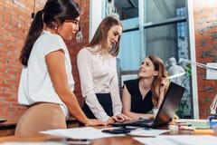 Creatief team die aan nieuw project werken die samen en aan hun partner kijken luisteren die zich rond bureau draagbaar gebruiken stock afbeeldingen