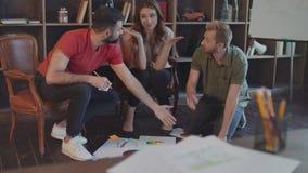 Creatief team die bedrijfsstrategiedocumenten op vloer in bureau bespreken stock videobeelden