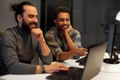 Creatief team met computer die laat op kantoor werken stock afbeeldingen