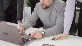Creatief team van bedrijfsmensen die en laptop het scherm bespreken bekijken stock videobeelden
