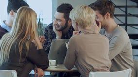 Creatief team van jonge ontwerpers die in hun bureau tijdens informele vergadering samenwerken stock footage