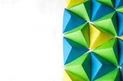 Creatieve achtergrond met blauwe, groene en gele origamitetrageders stock foto