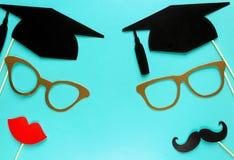 Creatieve achtergrond met photoboothsteunen voor graduatie: hoeden, diploma, glazen, lippen op heldere blauwe document achtergron stock afbeelding