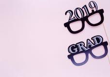 Creatieve achtergrond met photoboothsteunen voor graduatie: hoeden, diploma, glazen, lippen op pastelkleur roze document achtergr stock afbeeldingen