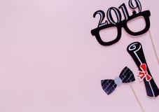 Creatieve achtergrond met photoboothsteunen voor graduatie: hoeden, diploma, glazen, lippen op pastelkleur roze document achtergr royalty-vrije stock afbeelding