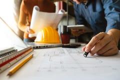 Creatieve architect die op de grote tekeningen ontwerpen stock afbeeldingen