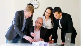 Creatieve commerciële teamvergadering die in in modern licht bureau nieuwe ideeën bespreken Zij die blauwdruk bekijken Werkgever stock videobeelden