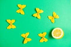 Creatieve die de zomerlay-out van citroen en gekleurd deegwarengriesmeel papillon wordt gemaakt op heldergroene achtergrond Fruit stock foto's