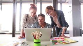 Creatieve directeur die laptop met zijn team bekijken en plannen bespreken stock video