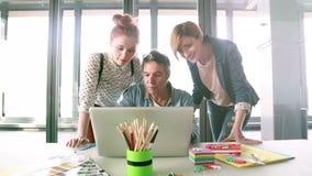 Creatieve directeur die laptop met zijn team bekijken en plannen bespreken stock footage