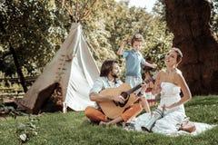 Creatieve familie die muzikale instrumenten spelen dichtbij tent stock foto's