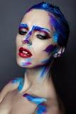 Creatieve kunstmake-up van een jong meisje met blauwe ogen royalty-vrije stock afbeeldingen