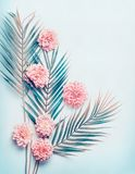 Creatieve lay-out met tropische palmbladen en pastelkleur roze bloemen op turkooise blauwe Desktopachtergrond, hoogste mening, pl royalty-vrije stock afbeelding