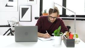 Creatieve manager het schrijven ideezitting in bureau stock footage
