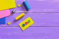 Creatieve manier om knopen aan het vilt te naaien Multicolored knopen op geel gevoeld stuk Schaar, draad, gevoeld vlak Stock Afbeeldingen