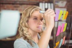 Creatieve onderneemster die op kleverige nota's in bureau schrijven Stock Afbeeldingen
