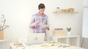 creatieve ontwerper die controlerend documenten, die in creatieve ruimte werken werken stock footage