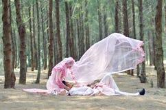 Creatieve openluchtphotoshoot van een malay houdende van paarbruid en een bruidegom stock afbeelding