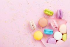 Creatieve samenstelling met envelop en cake macaron of makaron op roze pastelkleur hoogste mening als achtergrond Vlak leg stock afbeelding