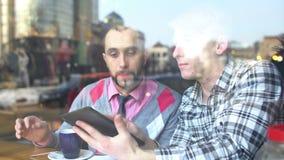 Creatieve vergadering in een koffie van twee jonge mensen stock videobeelden