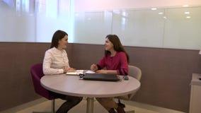 Creatieve vergadering van twee bedrijfsvrouwen in het bureau bij de lijst stock video