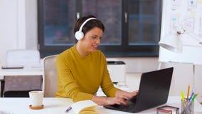 Creatieve vrouw in hoofdtelefoons met laptop op kantoor stock video