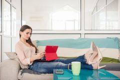 Creatieve vrouwenzitting op bank terwijl het werken aan tablet in het bureau stock afbeeldingen