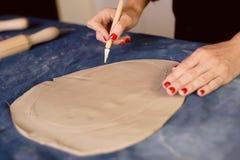 Creatieve workshop die van ceramist het In orde maken met een scalpel, tot de vorm leiden een aarden schotel Werkschema stock fotografie