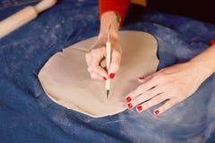 Creatieve workshop die van ceramist het In orde maken met een scalpel, tot de vorm leiden een aarden schotel Werkschema stock afbeelding