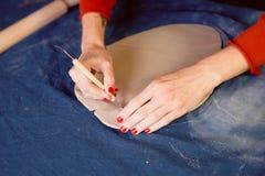 Creatieve workshop die van ceramist het In orde maken met een scalpel, tot de vorm leiden een aarden schotel Werkschema royalty-vrije stock afbeeldingen