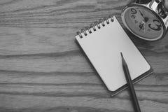 Creatieve zaken en Ideeconcept: Het gebruikte potlood zette op notitieboekje met zilveren wekker gezet op houten lijst royalty-vrije stock afbeelding