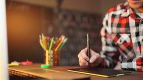 Creatieve zakenman die op grafische tablet schrijven terwijl het gebruiken van laptop in bureau stock video