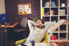 Creatieve zakenman het luisteren muziek bij bureau Stock Foto