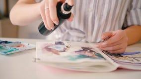 Creating artwork hand spraying watercolor painting. Creating artwork. Delicate woman hand spraying watercolor painting with water. Artist skill technique work stock footage