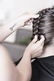 Creating a braided hairstyle. Professional hairdresser creating a braided hairstyle to her client stock photography