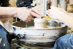 Creating a clay pot on potter`s wheel stock images
