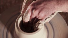 Creating earthenware and traditional pottery concept. Experienced male potter`s hands creating beautiful clay product - stock video footage