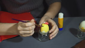 Creating easter chicken from the shell by hand on a grey table.
