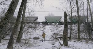 Creating footage of passing freight train in winter. Winter scene of man shooting video of freight train traveling in the countryside. Cameraman changing stock video footage