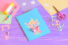 Creating a greeting card for mom. Step. Card with flowers made of colored paper. Materials for kids art on a wooden table Stock Photo