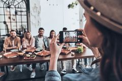 Creating happy memories. Young women photographing a group of her friends using smart phone while they having a dinner party royalty free stock photos