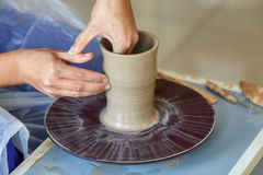 Creating jar or vase of clay. Woman hands, potter`s wheel Royalty Free Stock Photo
