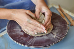 Creating jar or vase of clay. Woman hands, potter`s wheel Stock Photography