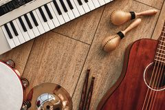 Creating a melody...Top view of musical instruments set: synthesizer, electronic guitar, wooden drum sticks, golden. Cymbal, drums, gold maracas and tambourine stock images