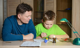 Creating the model plane. Happy son and his father are making aircraft model. Hobby and family concept. Making the model plane. Happy son and his father are Stock Image