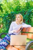 Creating new content for her blog. Girl blogger works outdoor with laptop and smartphone. Woman works on web blog in. Park. Girl freelancer successful blogger stock photos