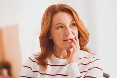 Attractive young woman touching her face. Creating plan. Beautiful female person looking aside while being deep in thoughts Royalty Free Stock Photography