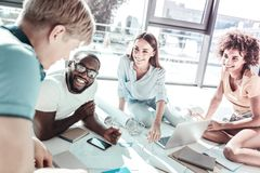 Positive delighted colleagues discussing new project. Creating plan. Pretty females sitting on the floor and listening to their partners, being in the office royalty free stock photos